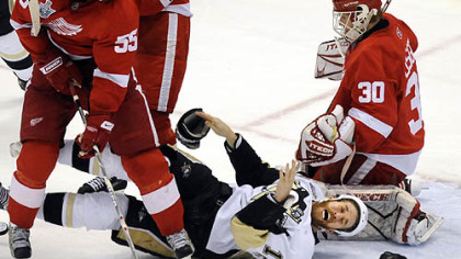 Ryan Malone loses his gloves in between the Red Wings' Niklas Kronwall and Chris Osgood in the second period Monday night.