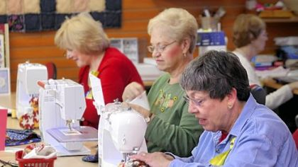 Margie McGinn, left, of Murrysville, Jean Laverty, of Lower Burrell, and Maire Machens, of Murrysville, sew holiday stockings to be filled with treats and sent to soldiers abroad at Gloria Horn Sewing Studio in Monroeville.