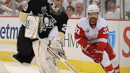 Marc-Andre Fleury handles the puck past the Red Wings' Kris Draper.