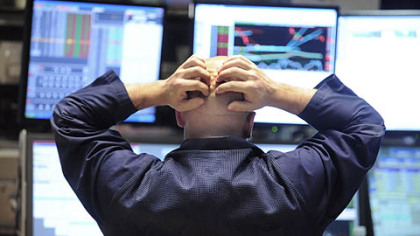 Specialist Justin Bohan holds his head as he works at his post on the floor of the New York Stock Exchange yesterday. Stocks plunged in the final minutes of trading, sending the Dow Jones industrial average down more than 675 points.