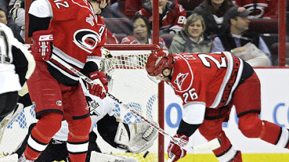 The Hurricanes' Erik Cole, right, scores against Penguins goalie Dany Sabourin as Eric Staal (12) looks on in the first period last night in Raleigh, N.C.