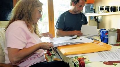 Cindy and Randy Balzer, sitting in the kitchen of their Baldwin Township home, look over stacks of paperwork as they try to save their home from foreclosure.