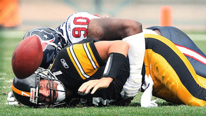 Williams lies on Roethlisberger after causing a fumble.