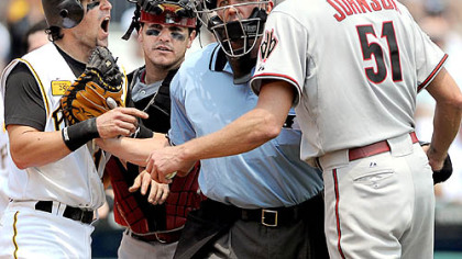 Doug Mientkiewicz, left, and Diamondbacks starter Randy Johnson are restrained by umpire Jeff Kellogg and Arizona catcher Miguel Montero in the third inning yesterday at PNC Park.