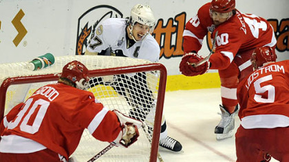 Detroit's  Henrik Zetterberg, rear, and Nicklas Lidstrom converge on Sidney Crosby behind Red Wings goaltender Chris Osgood in the first period.