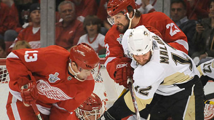 Red Wings goalie Chris Osgood gets help from a few friends in keeping Ryan Malone at bay last night.