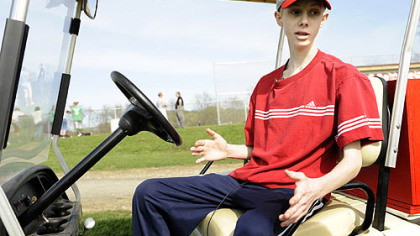 At his team's baseball game, John Challis uses a golf cart to get around.