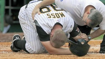 The Pirates' Brandon Moss is checked by athletic trainer Brad Henderson after spraining his left ankle in the seventh inning.