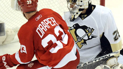 Detroit&#039;s Kris Draper crashes the net on Marc-Andre Fleury as the puck caroms off the crossbar last night.