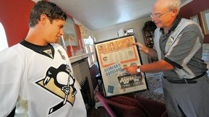 Sidney Crosby is shown the score sheet from 1967 by lifelong season-ticket holder David Disney after Crosby delivered Disney's season tickets yesterday. It marks the second season Penguins players helped deliver the tickets to their fan base.