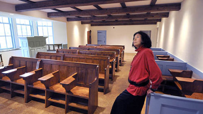 "E. Maxine Bruhns leans on the ""box pews""  in the Welsh Nationality Classroom."