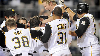 Jason Michaels leaps onto home plate as his Pirates teammates surround him in the aftermath of him hitting a game-winning home run last night against the Cardinals.