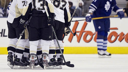 Penguins players celebrate a goal by Mark Eaton as Toronto Maple Leafs defenseman Pavel Kubina, right, skates by during second period preseason hockey action yesterday in Toronto.