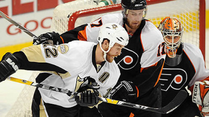Penguins Ryan Malone tries to tip the puck in past Flyers goalie Martin Biron.