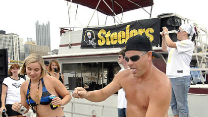 "Fans Laura Sendacook of South Park and ""Goob"" Jenkins of West View dance to the music from a disc jockey aboard one of the ""Steelers' Navy"" boats outside Heinz Field."