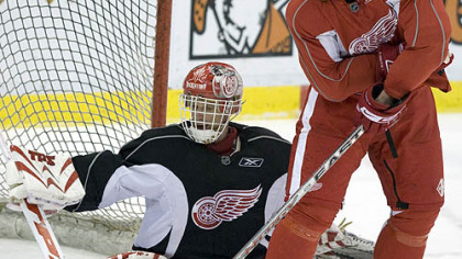 Detroit right winger Johan Franzen battles for the puck with goaltender Dominik Hasek yesterday in practice. Franzen could return to the Red Wings' lineup for Game 2 in Detroit tonight.