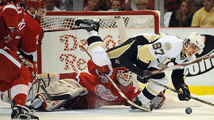 Detroit goalie Chris Osgood makes a save on Sidney Crosby in the first period last night.