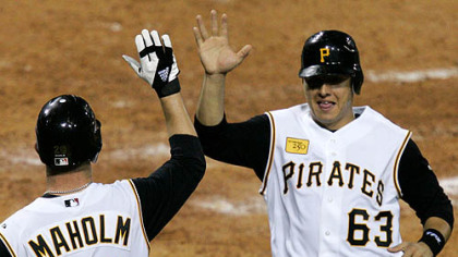 Paul Maholm (28) and teammate Luis Cruz (63) score on a three-run fifth-inning double by Pirates' Nate McLouth in a baseball game against the St. Louis Cardinals at PNC Park last night.