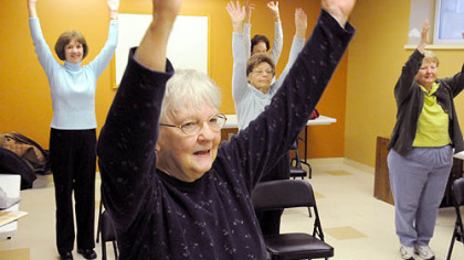 Sue Beard of McCandless holds her arms up with her classmates during the exercise session held at the Ingomar United Methodist Church. She has been with the class for four years and is certified as an instructor.