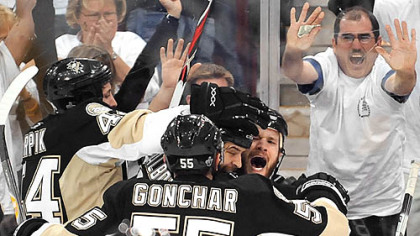 The Penguins' Adam Hall (right  with mouth open) is mobbed by teammates after scoring in the third period.