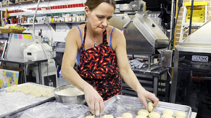 Linda Jones dips dough balls in flour before a machine flattens them into warm tortillas at Reyna Foods on Penn Avenue in the Strip District. Reyna recently started making its own corn and wheat-flour tortillas.