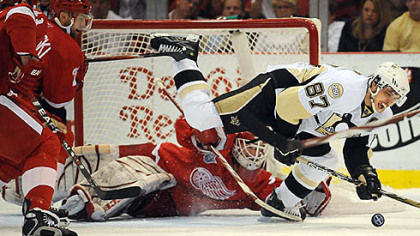 Red Wings goalie Chris Osgood makes a save on Sidney Crosby last night.