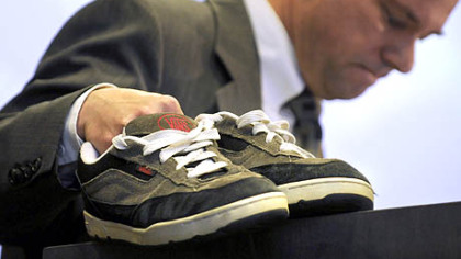 While addressing the National Symposium on Handgun Violence at Duquesne University, Tom Mauser displays the shoes of his son, Daniel, who was killed at Columbine High School. Mr. Hauser wears the shoes on special occasions.