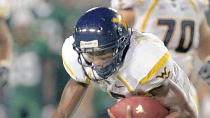 West Virginia's Pat White is tripped up by South Florida's Jerome Murphy in September 2007.  The Bulls won, 21-13.