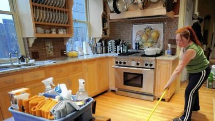 Heather Kniess of Shiny Happy Cleaners swabs the decks in a client's kitchen in the Mexican War Streets on the North Side with a diluted vinegar-and-water solution. The solution leaves no residue on the hardwood floor that can catch dirt later or discolor the wood.