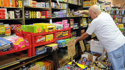 Bill McCoy of McKeesport, straightens the shelves piled with candy at the Fort Pitt Candy Company in the Strip.