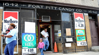 Bill McCoy of McKeesport, carries an order to the car for Zena Stafford, Allentown (with granddaughter, Zena, 2, in tow) at the Fort Pitt Candy Company in the Strip.