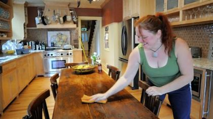 Here she uses a natural almond oil solution to clean a wooden table.