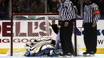 Officials look for -- and find -- the puck beneath the pile of goalie equipment that is Dany Sabourin and determine that he had, in fact, made the save that beat the Islanders.