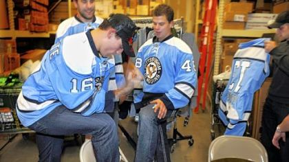 "Penguins players Paul Bissonnette, front, Eric Godard, left, Tyler Kennedy and Alex Goligoski  joke around while posing for photos after an event at Dick's Sporting Goods in Robinson showcasing the blue ""throwback"" Penguins hockey jerseys."