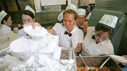 Waitresses prepare beignets covered with powdered sugar at Cafe du Monde, one of the most popular tourist spots in New Orleans' French Quarter.
