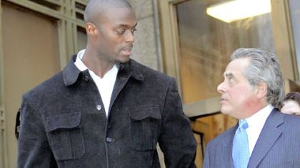 The Giants' Plaxico Burress, accompanied by his lawyer Benjamin Brafman, leaves Manhattan Supreme Court yesterday after his arraignment on weapons possession charges stemming from an incident at a Manhattan nightclub Friday.