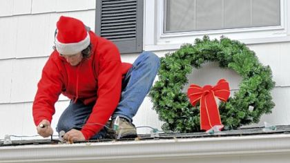 A volunteer crew from Elf Entertainment decorates the North Huntingdon home of a Lepley family in a contest that chose the families of two soldiers stationed in Iraq for free holiday decorations.