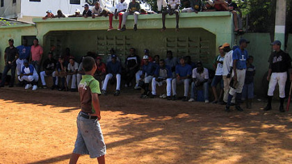 A Dominican child checks out the scene where tryout candidates await their turn in the dugout and neighborhood children pile onto the dugout roof.